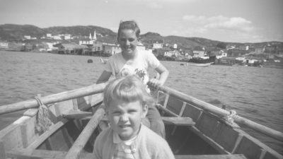 Children rowing a traditional wooden boat in Newfoundland